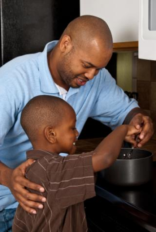 African American father teaching his son how to cook