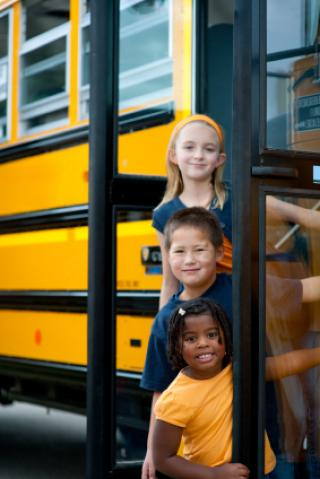 Diverse group of children and a school bus