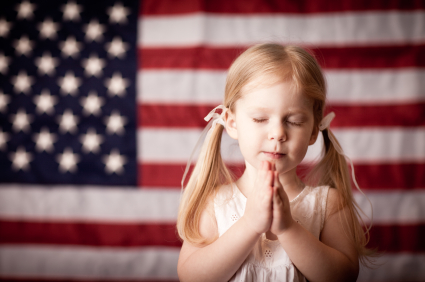Girl Praying with Flag in Background
